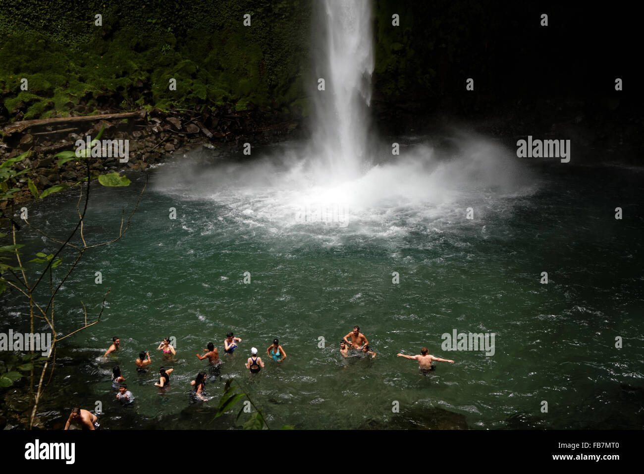 People swim in a pool at the bottom of a waterfall emerging from the jungle in Arenal Volcano National Park in Costa - Stock Image