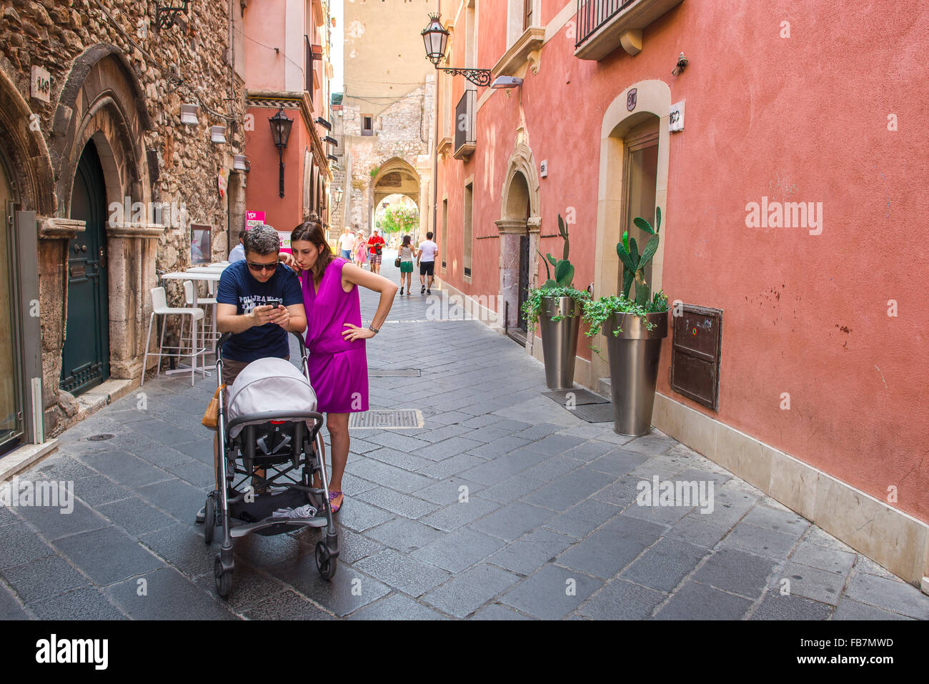 Couple looking phone, view of a young couple with a pushchair pausing in a street in Taormina, Sicily, to look at - Stock Image
