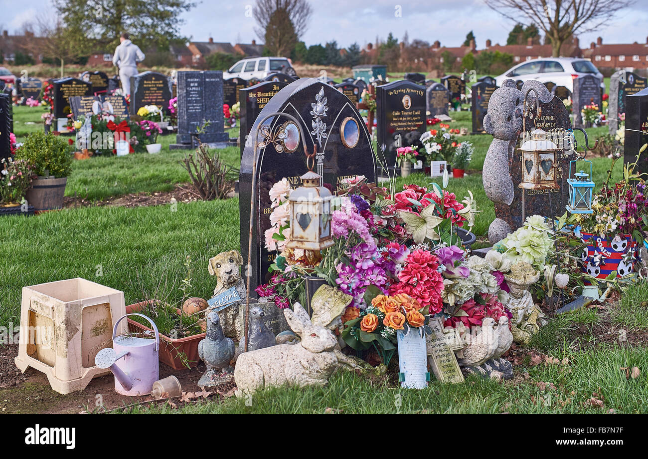 Gravestones at a cemetery in Hull decorated with memorial ornaments - Stock Image