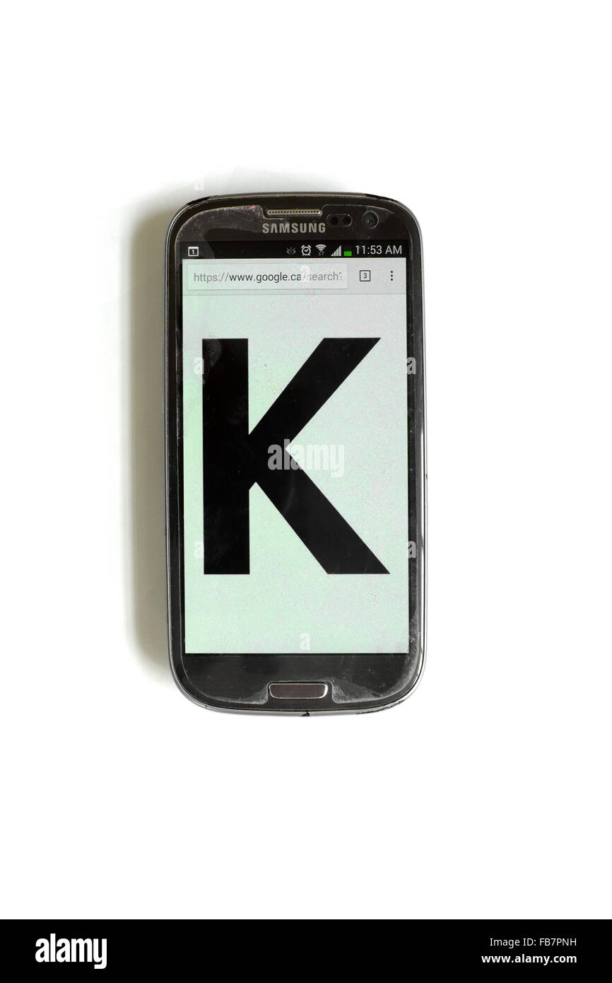The letter K written on the screen of a smartphone photographed against a white background. - Stock Image