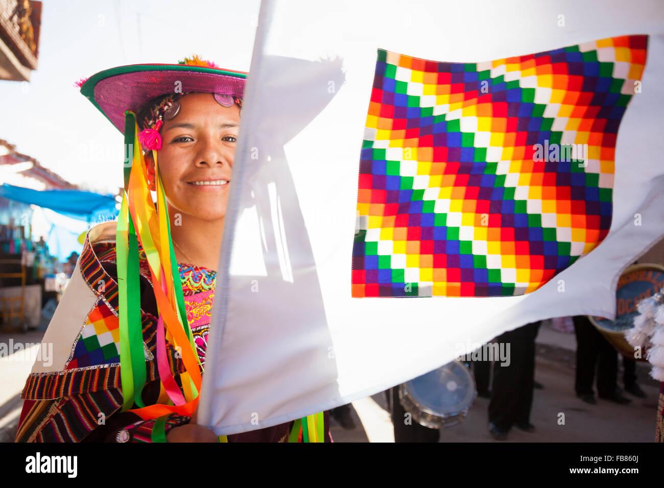 Dancer performing the 'dance of the llama herder' and waving the Aymara flag at the Fiesta de Nuestra Señora - Stock Image