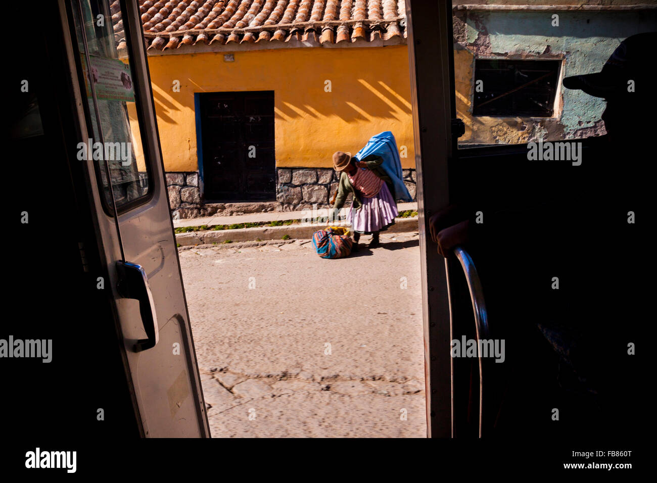 A cholita gathers her things for a mini-bus ride in Potosi, Bolivia. - Stock Image