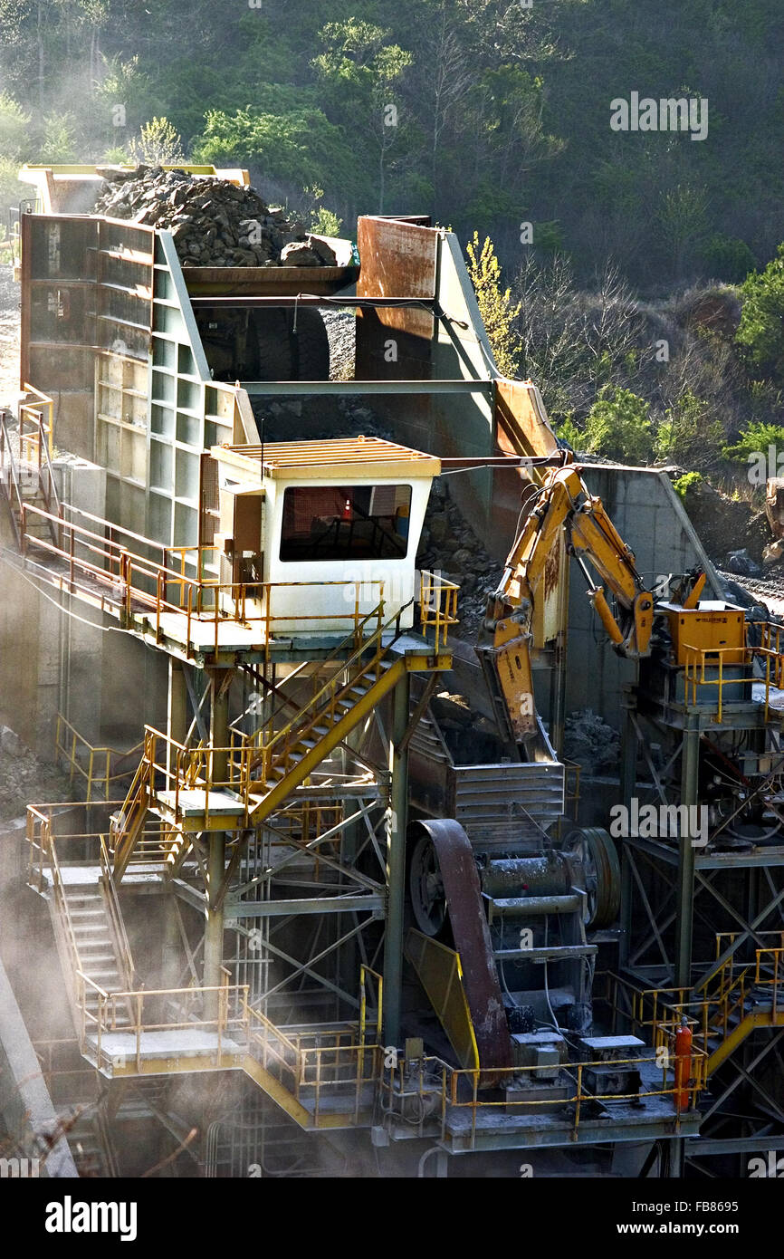 Chunks of blasted stone is dumped into a crusher which will process it into smaller size rock at a quarry. - Stock Image