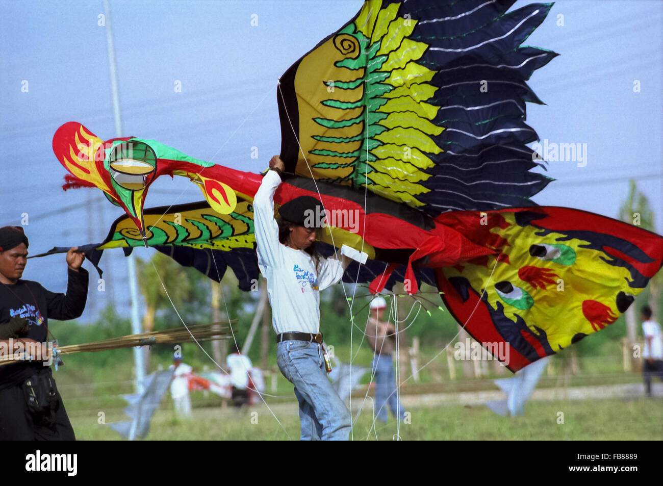 Men carry a large kite in the shape of bird during the Jakarta International Kite Festival at Carnival Beach, Ancol, North Jakarta, July 09-11, 2004. Stock Photo