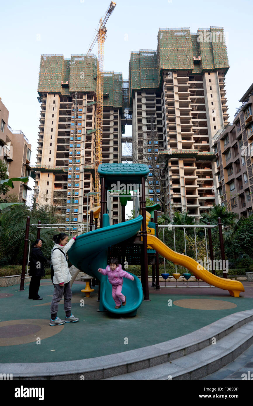 A toddler plays at the playground of a gated community while the complex of flats continues to expand with highrise - Stock Image