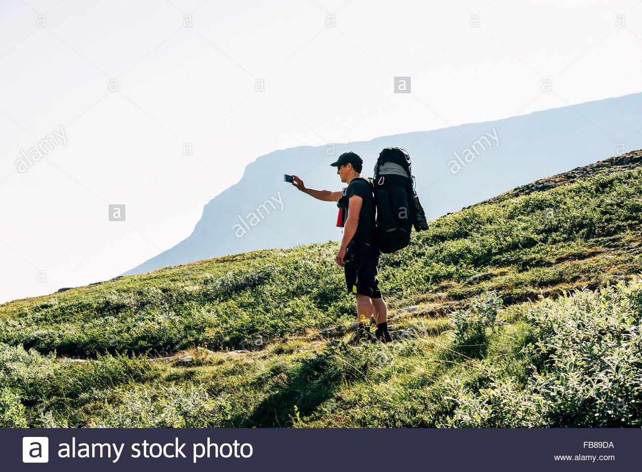 Sweden, Lapland, Ladtjovagge, Kungsleden, Male hiker making selfie with smart phone - Stock Image