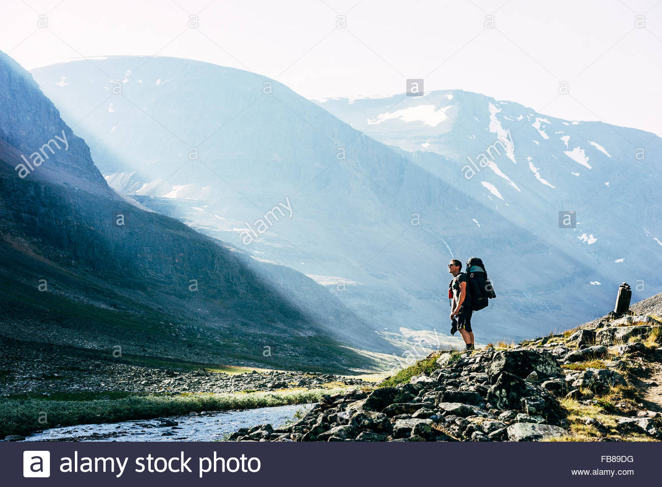 Sweden, Lapland, Ladtjovagge, Kungsleden, Male hiker standing by river in mountain valley - Stock Image