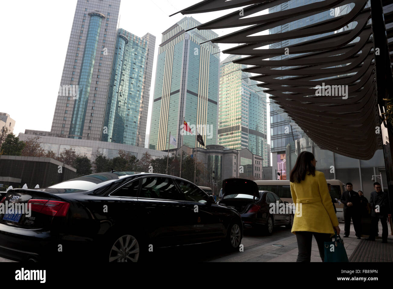 Limousines parked outside an upscale hotel amid a glut of high-rise buildings at the centre of Chengdu in China. - Stock Image