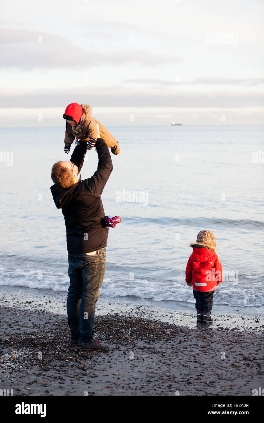 Denmark, Grenen, Father with daughters (6-11 months) ( 2-3) playing on beach Stock Photo
