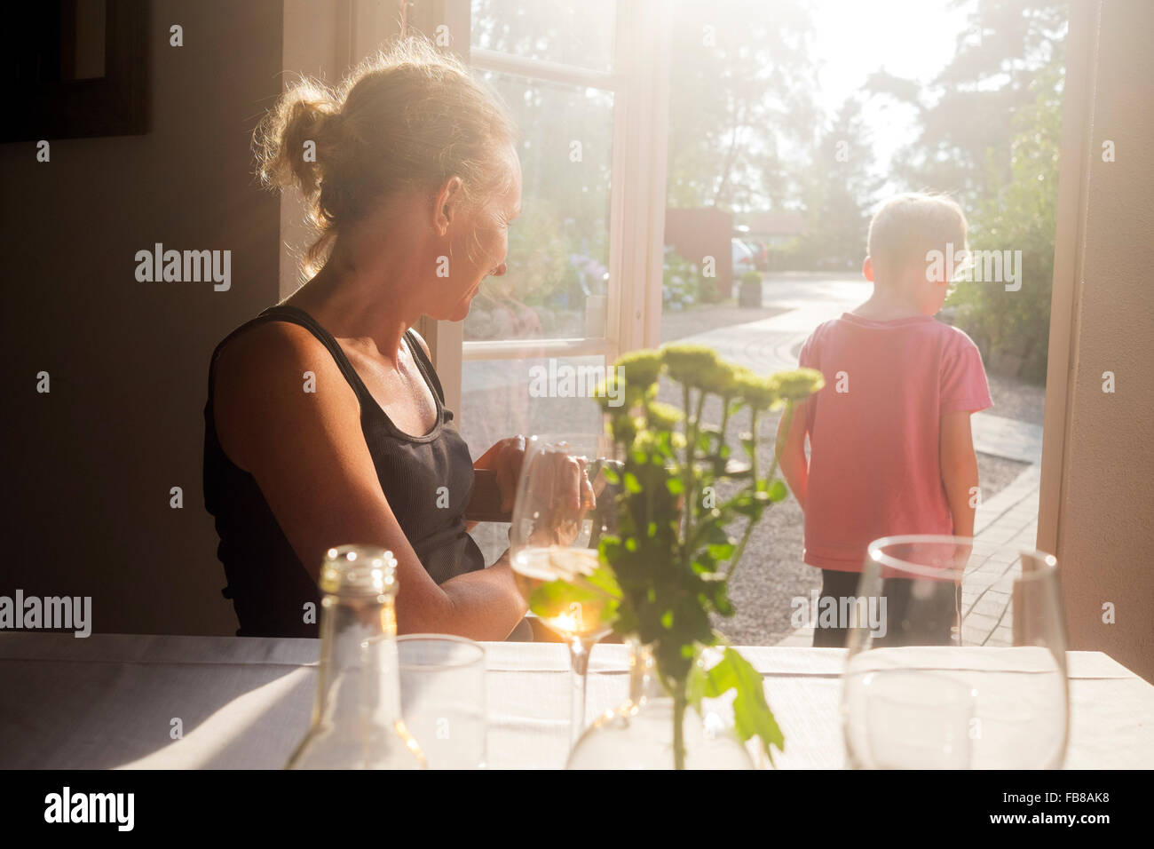 Sweden, Skane, Kullaberg, Mother looking at son (6-7) standing in doorway to backyard at restaurant - Stock Image
