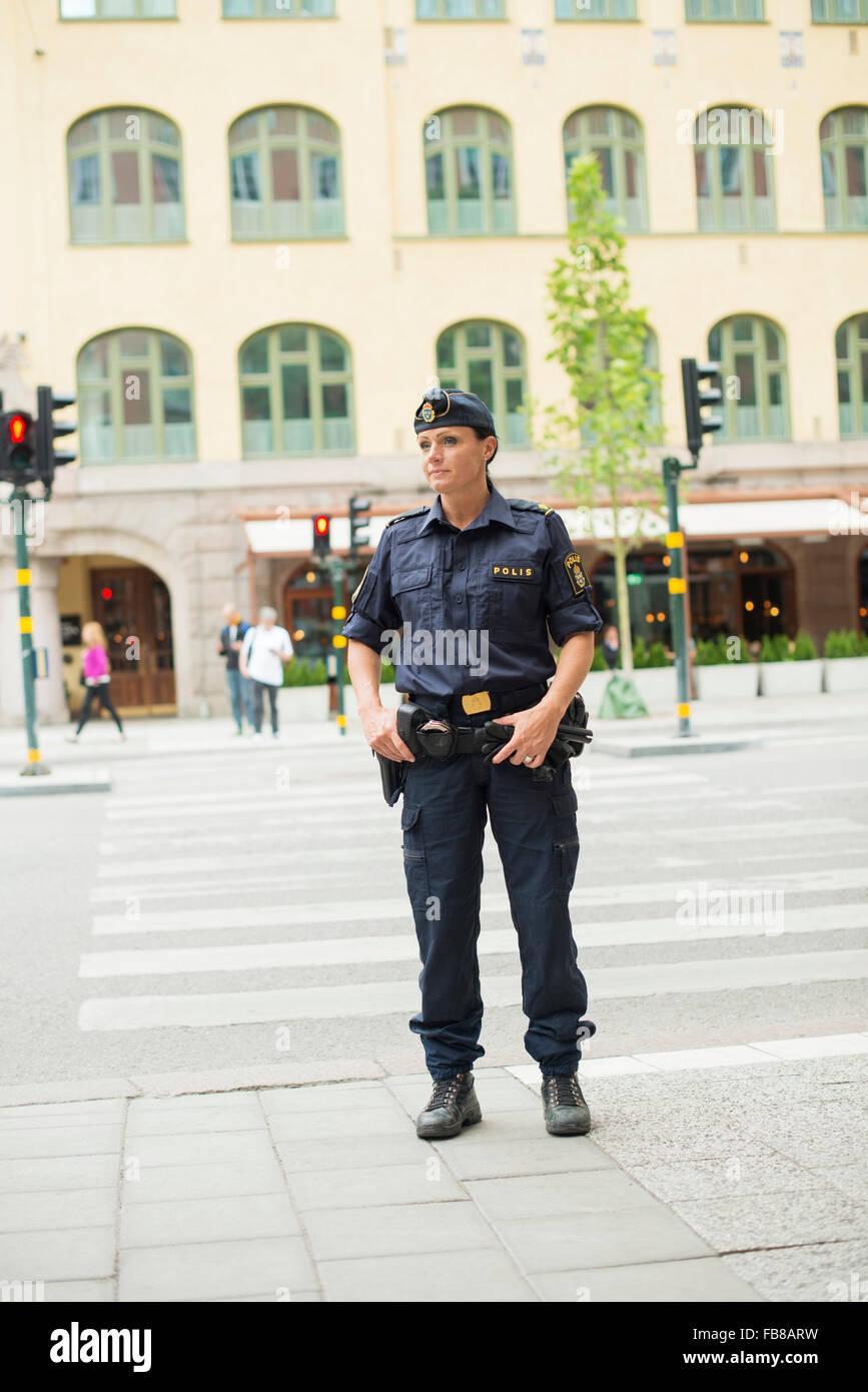 Sweden, Uppland, Stockholm, Policewoman looking away - Stock Image