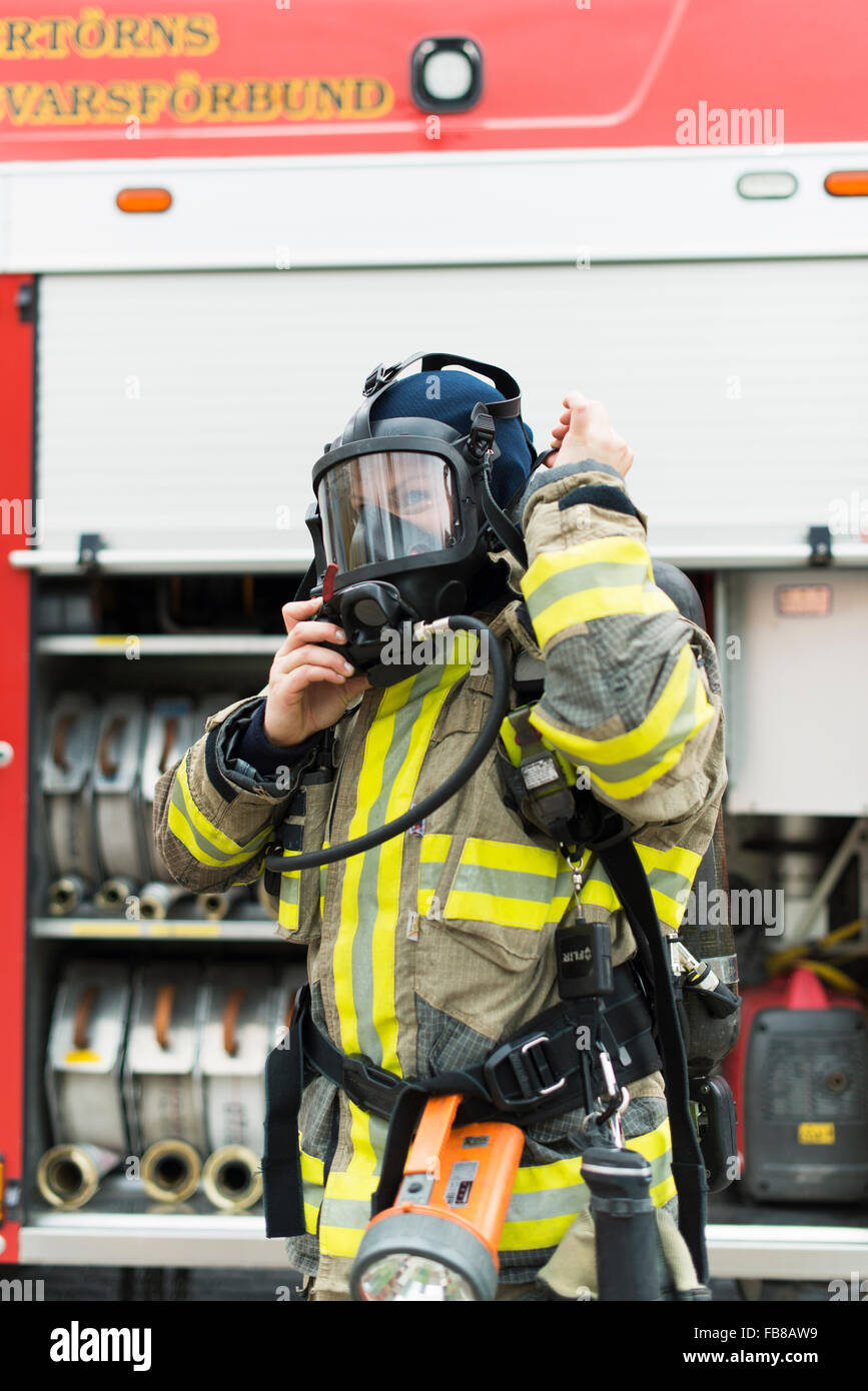 Sweden, Female firefighter putting on protective mask - Stock Image