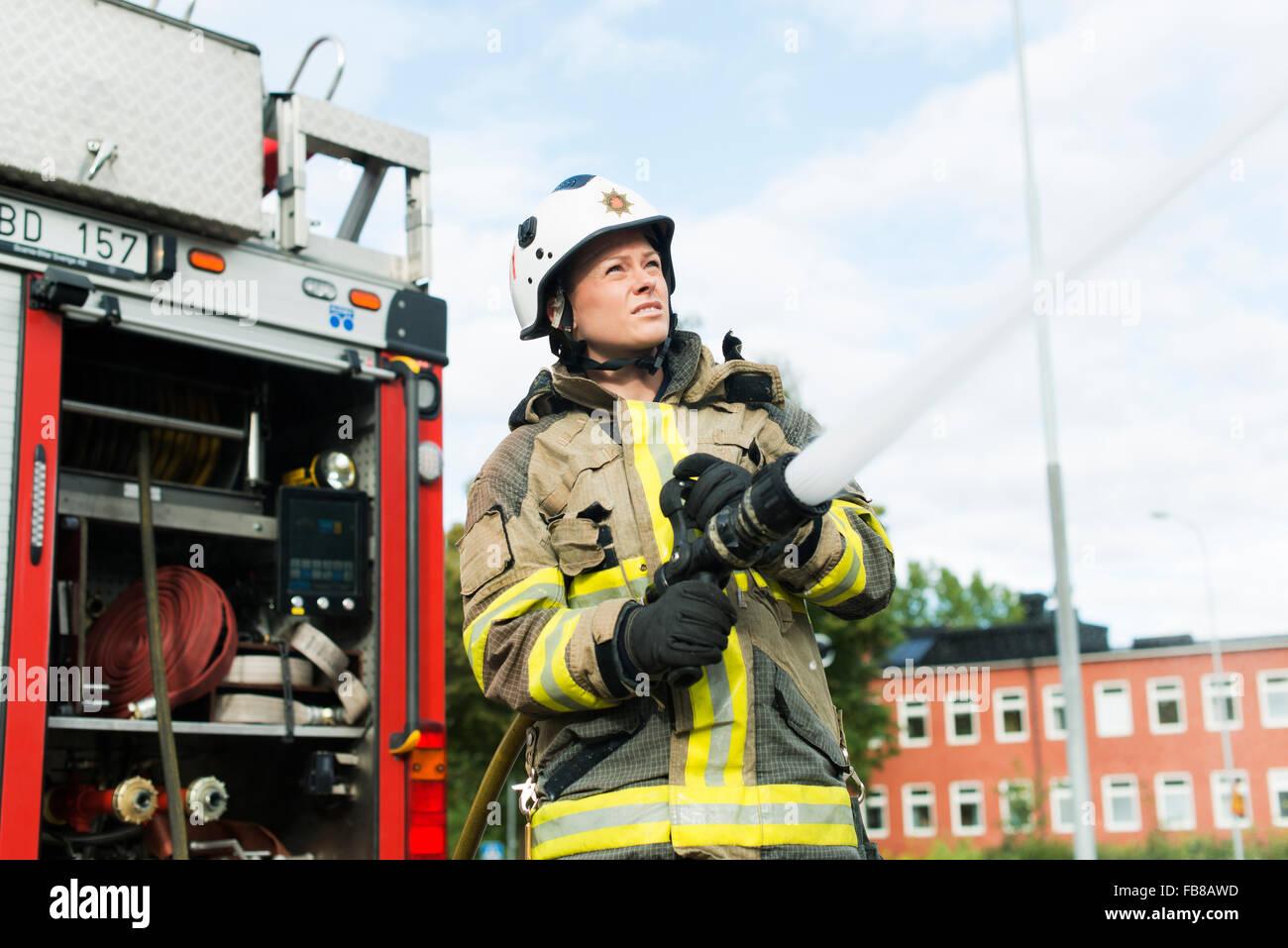 Sweden, Sodermanland, Sodertalje, Female firefighter using fire hose next to truck - Stock Image