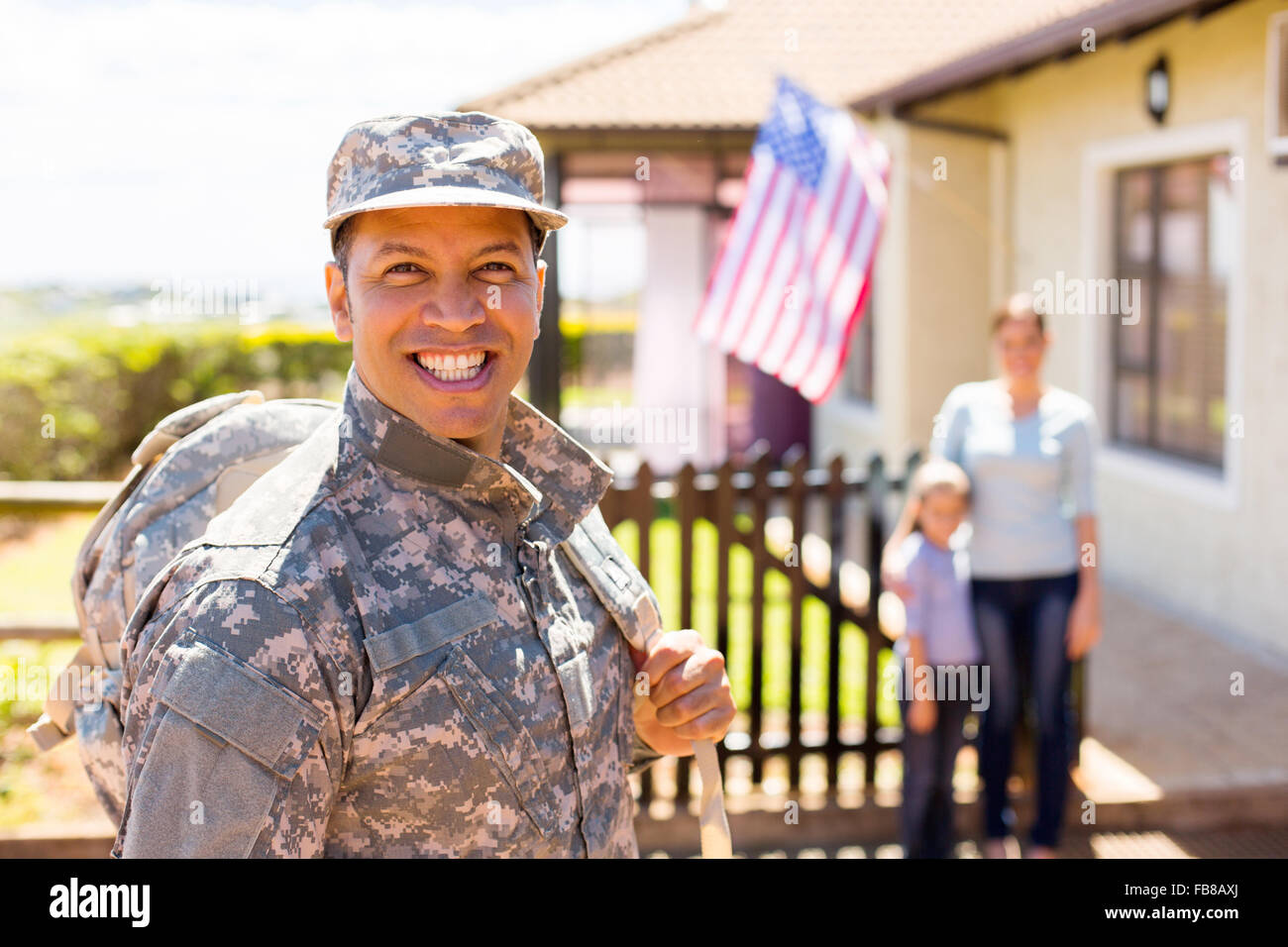 happy soldier returning home with family on background - Stock Image