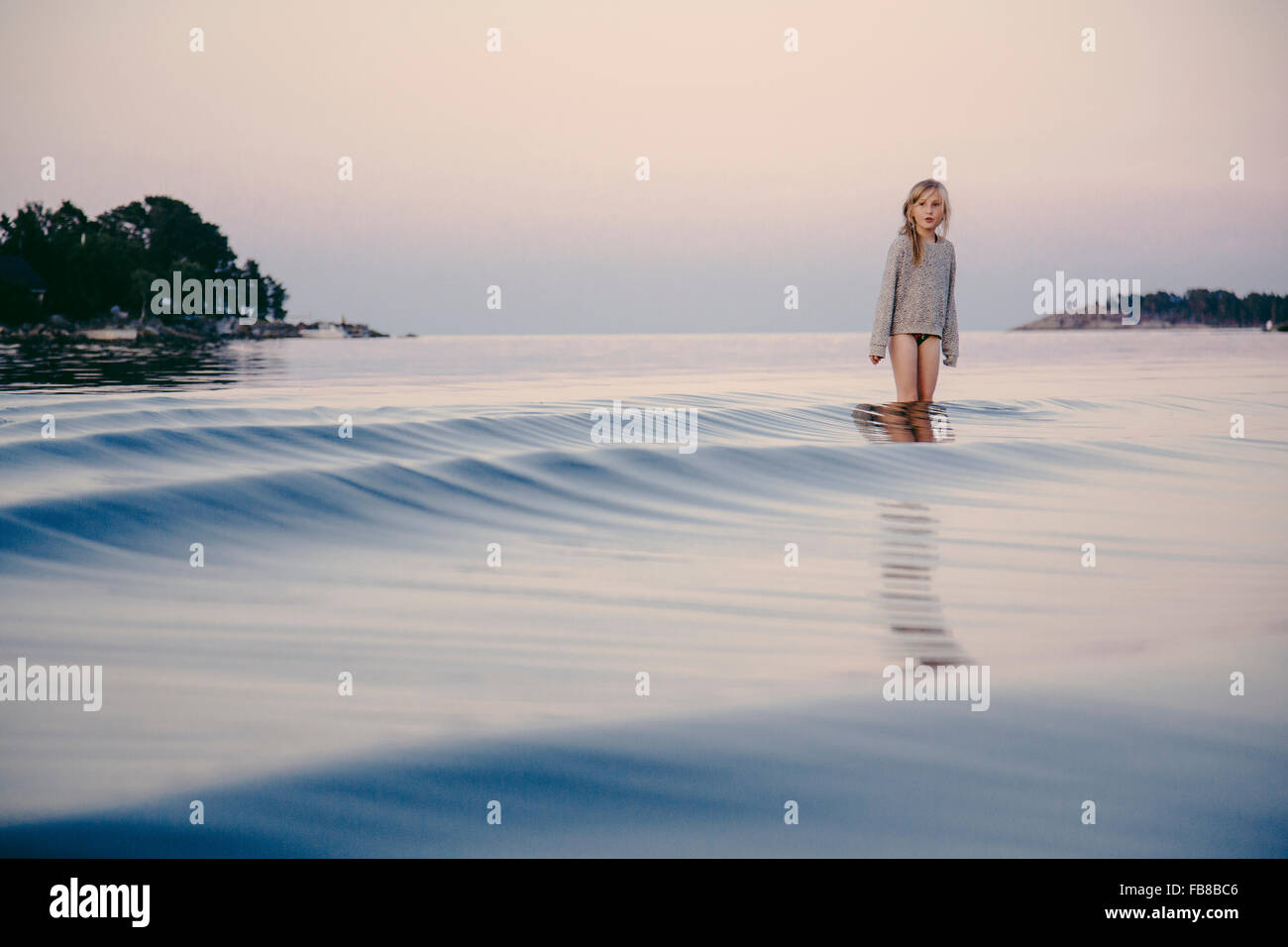 Sweden, Medelpad, Sundsvall, Juniskar, Girl (8-9) standing in water - Stock Image