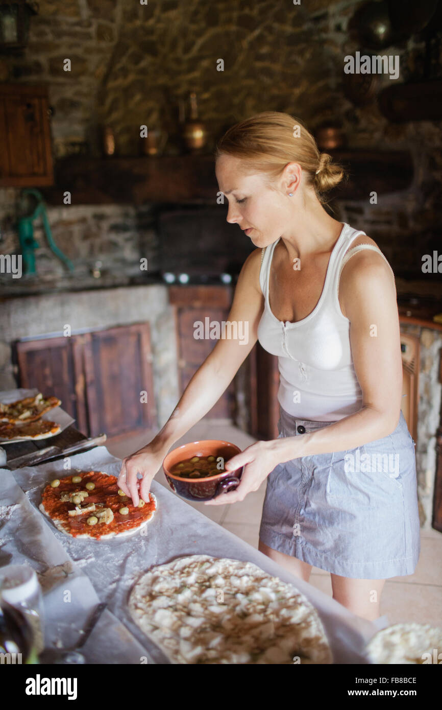 Italy, Tuscany, Woman preparing homemade pizzas - Stock Image