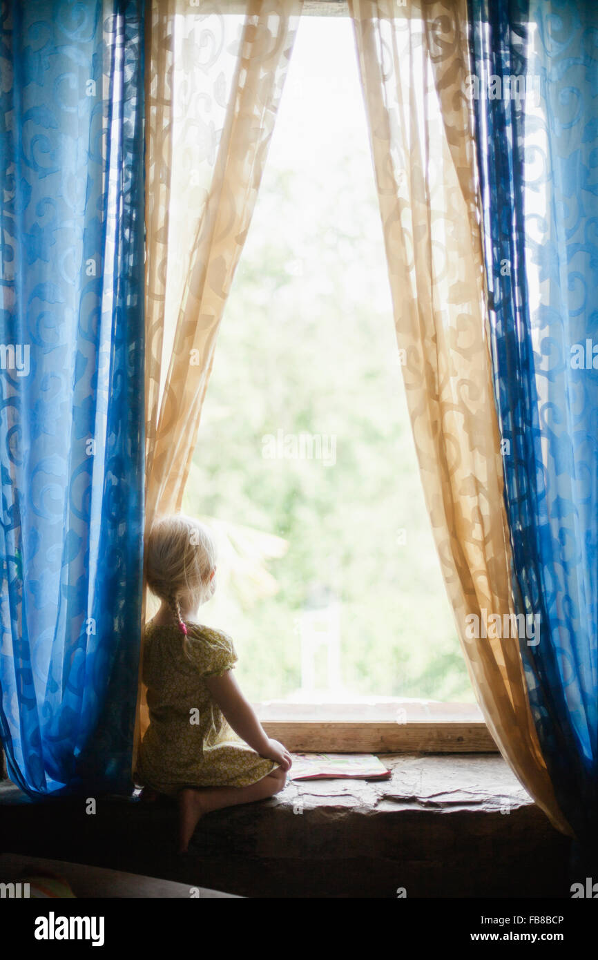Italy, Tuscany, Girl (2-3) looking through window - Stock Image