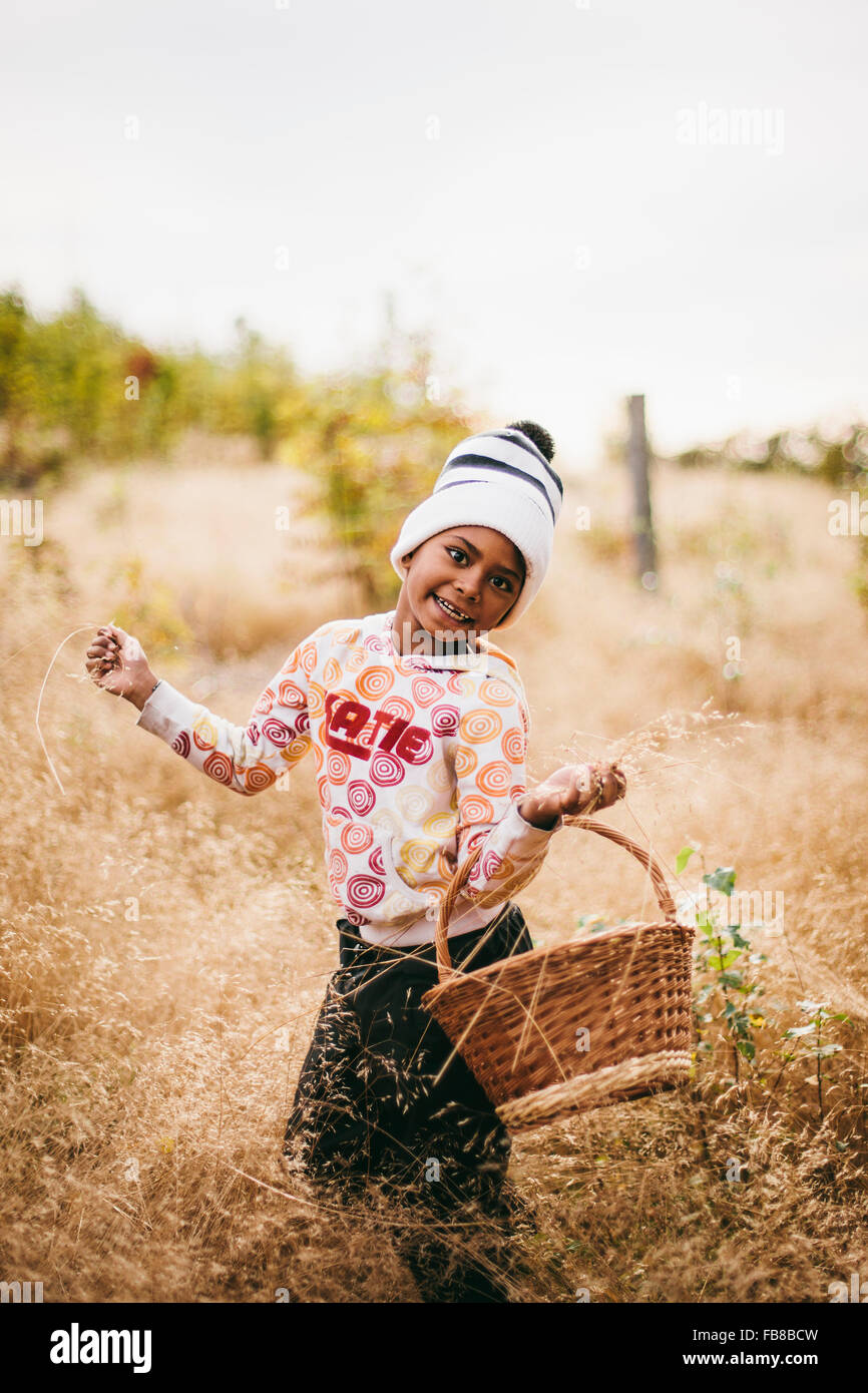 Sweden, Medelpad, Sundsvall, Juniskar, Portrait of smiling girl (6-7) holding basket - Stock Image