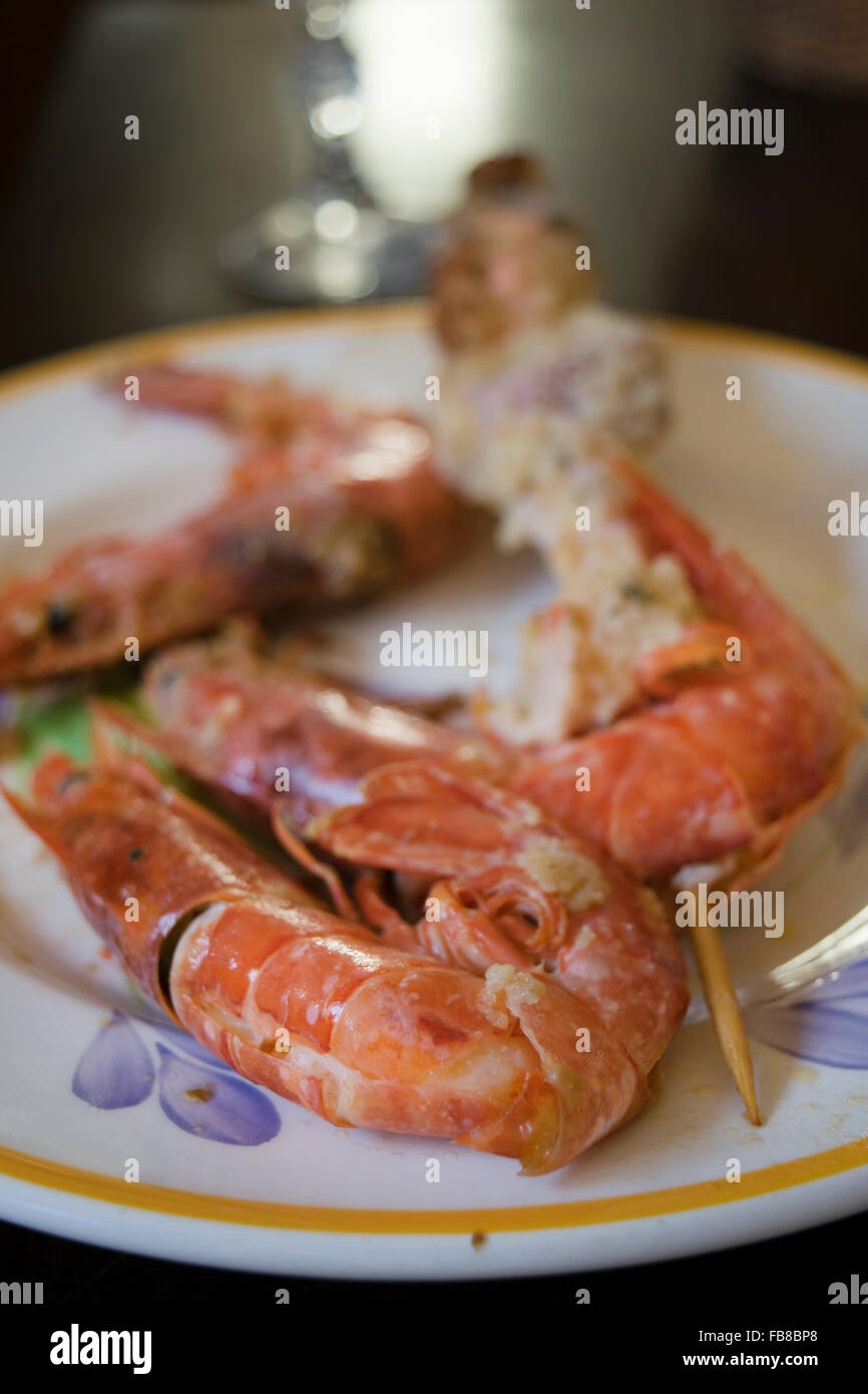 breaded and fried skewers of fish with near some jumbo prawns - Stock Image