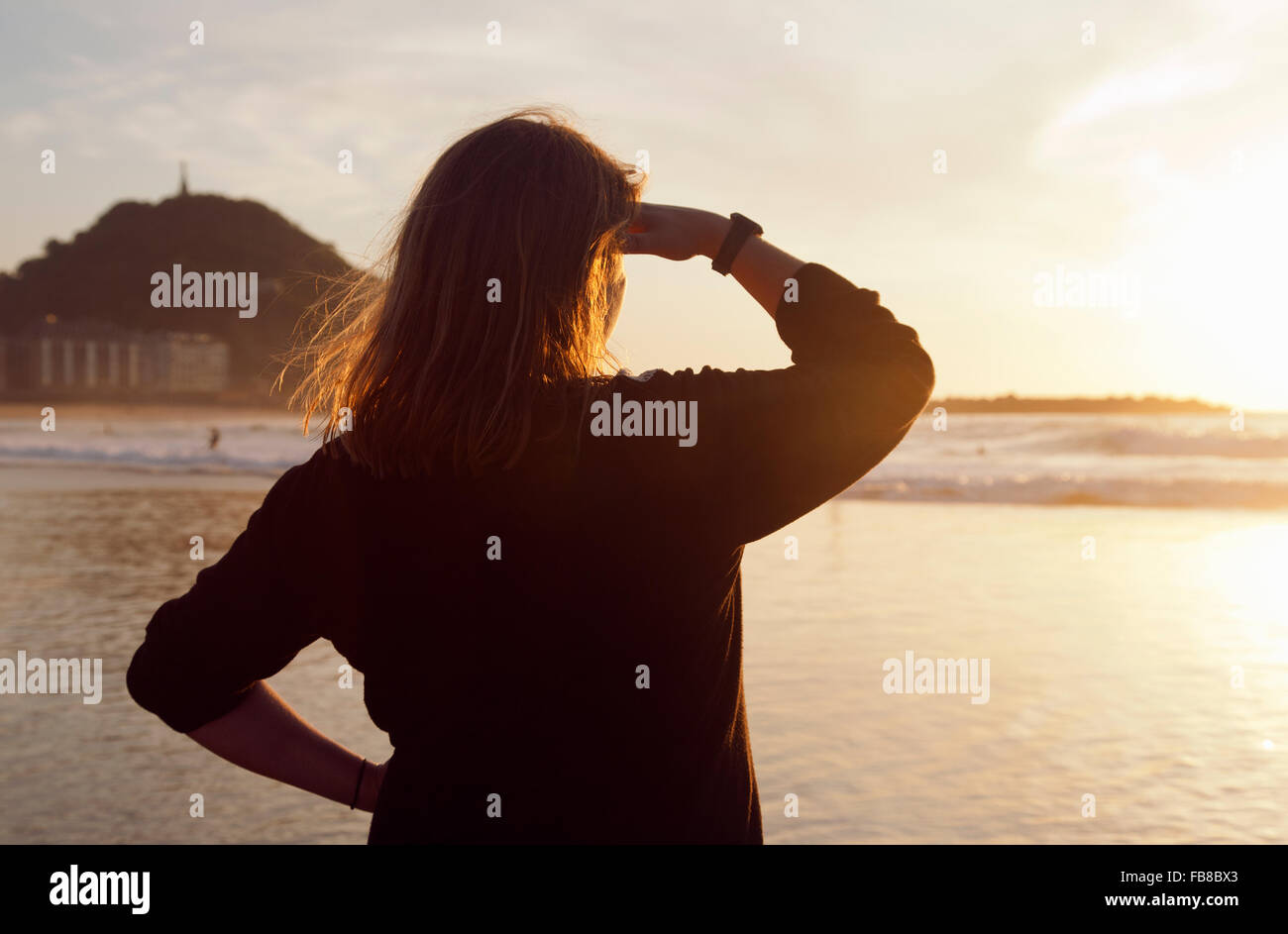 Spain, The Basque Country, Gipuzkoa, San Sebastian, Woman standing on beach and looking at Bay of Biscay at sunset - Stock Image