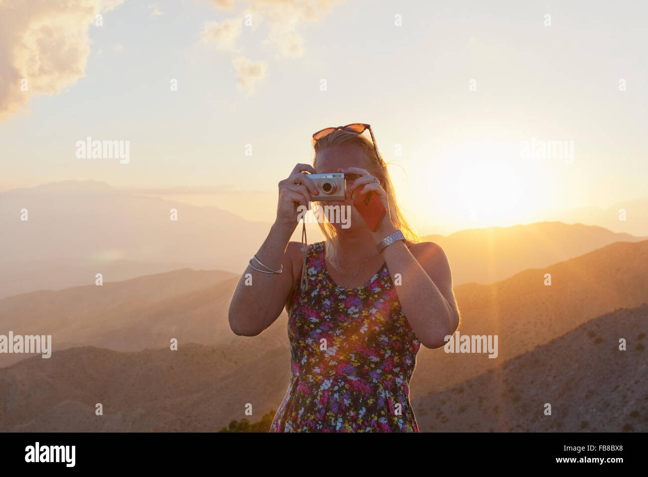USA, California, Joshua Tree National Park, Female tourist photographing landscape at sunset - Stock Image