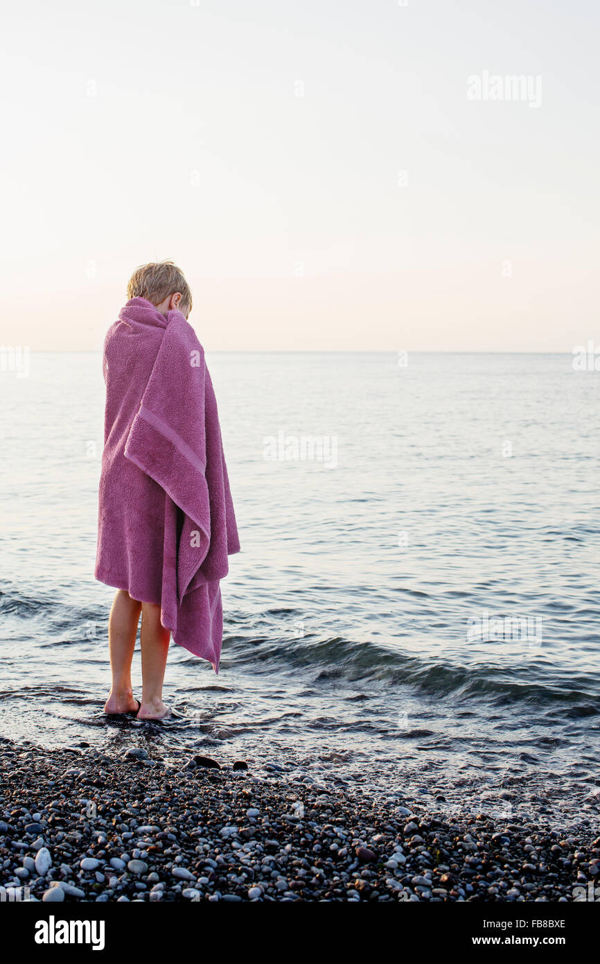Sweden, Gotland, Lickershamn, Boy (8-9) wrapped in towel standing at seashore at sunset - Stock Image