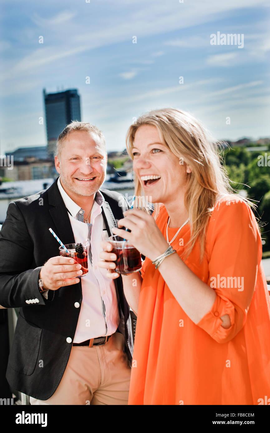 Sweden, Uppland, Stockholm, Portrait of couple drinking cocktails - Stock Image