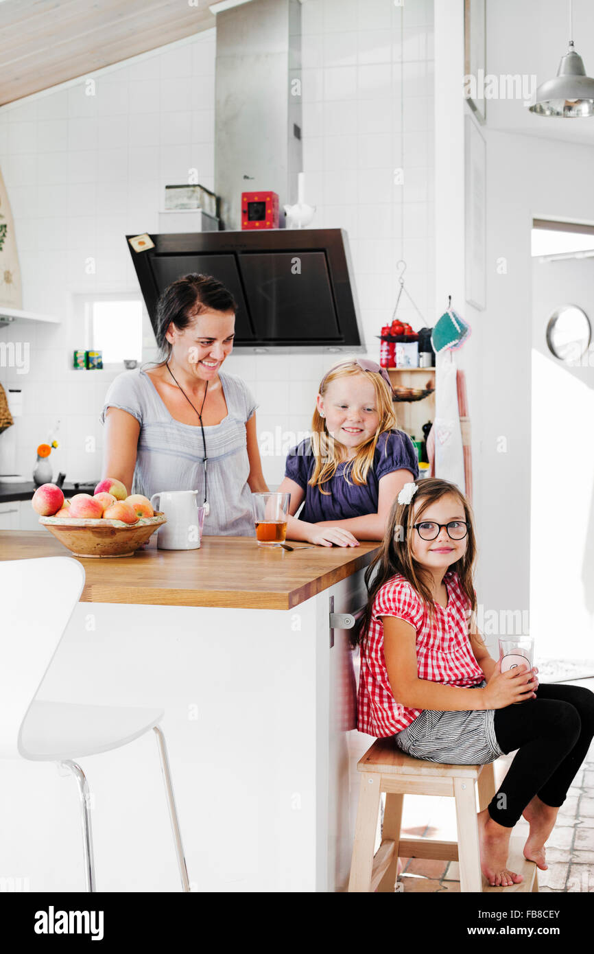Sweden, Mother and daughters (6-7, 8-9) smiling in kitchen - Stock Image
