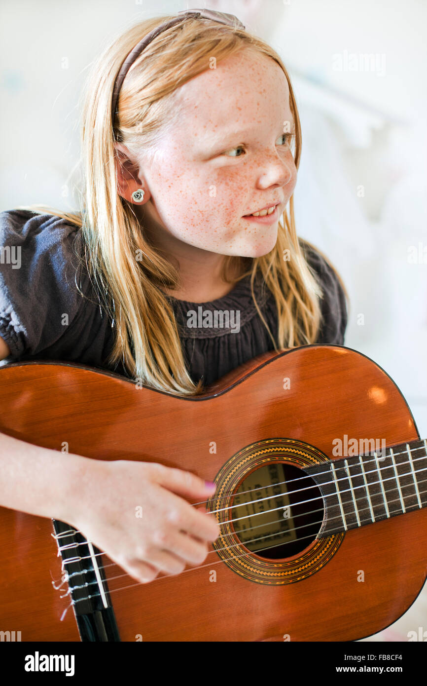 Sweden, Girl (8-9) playing guitar - Stock Image