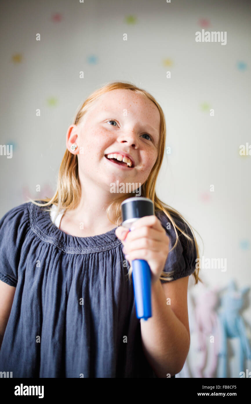 Sweden, Girl (8-9) singing karaoke - Stock Image