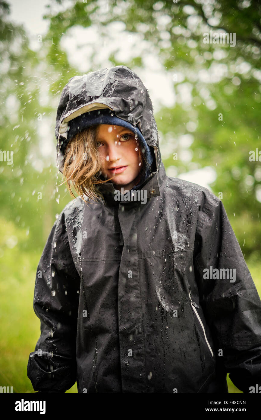 Sweden, Uppland, Blond girl (8-9) in raincoat - Stock Image