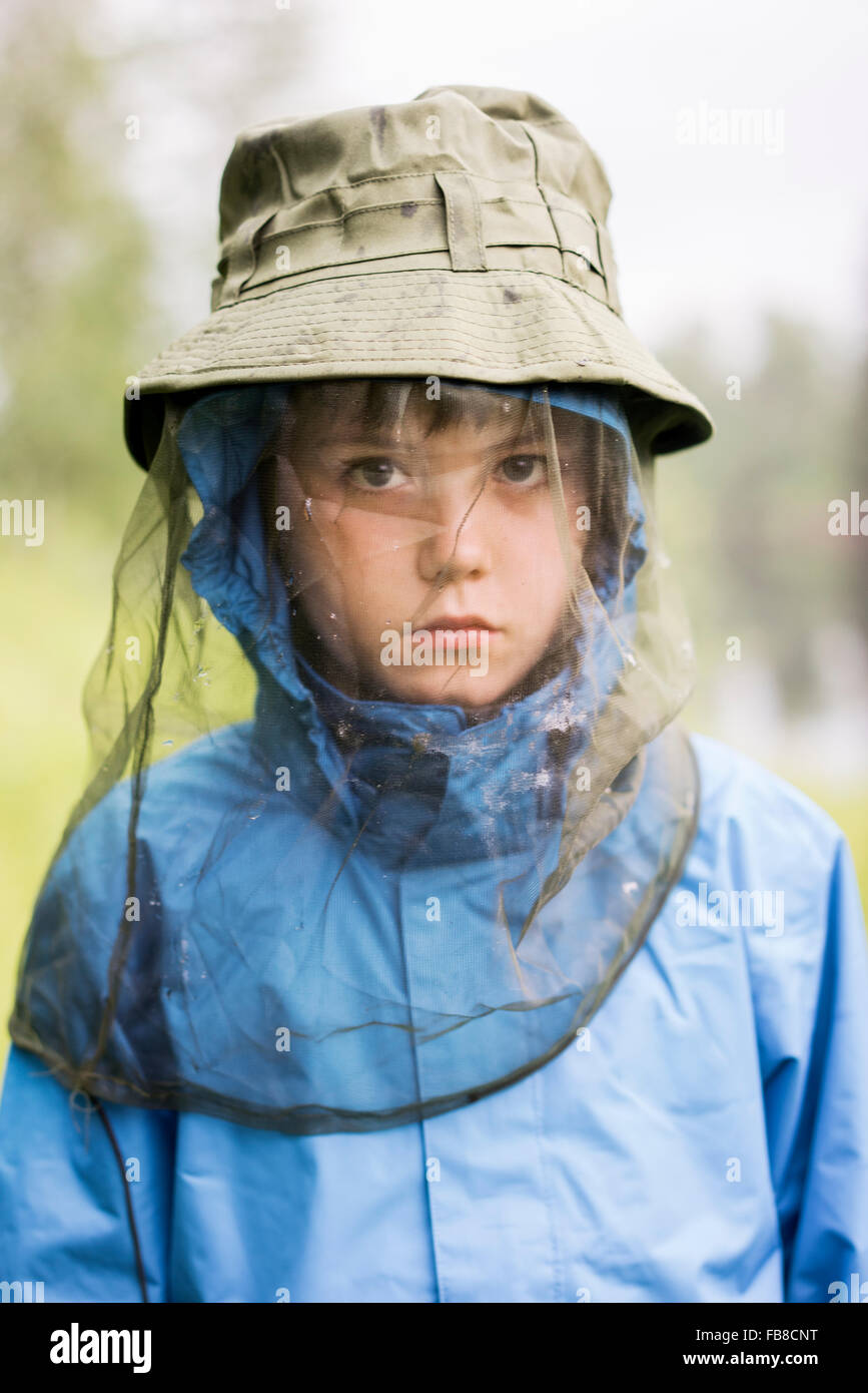 Sweden, Boy (10-11) wearing hat with protective net - Stock Image