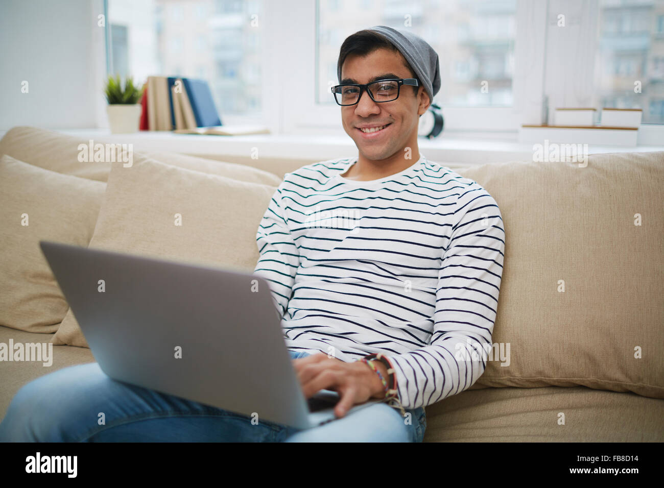Handsome guy in casual-wear networking and looking at camera - Stock Image