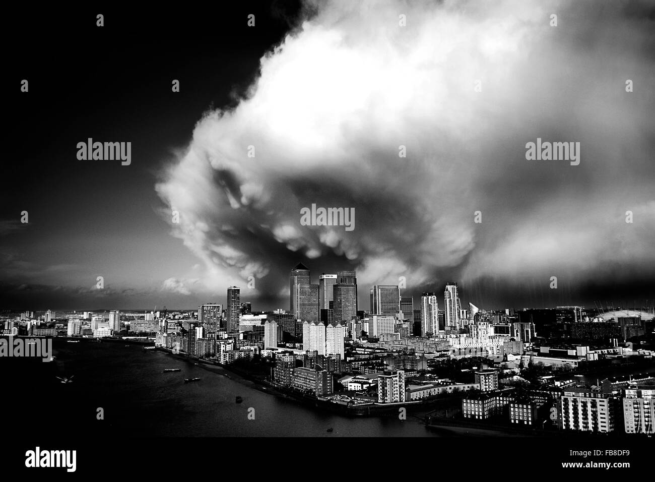 Large dramatic storm cloud rolling in over Canary Wharf London. Black and white cityscape. Skyscrapers by the River - Stock Image