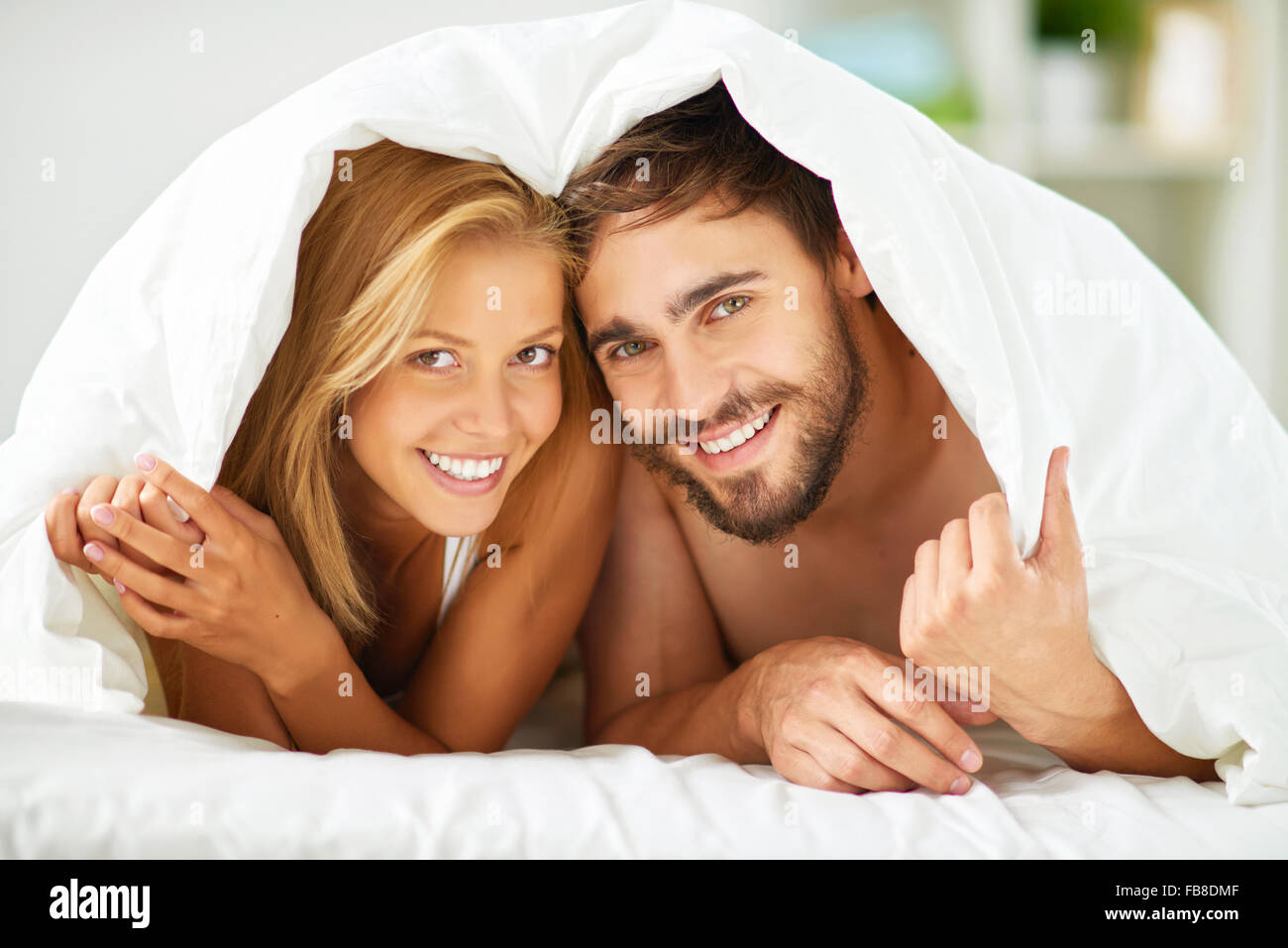 Happy dates under blanket looking at camera with smiles - Stock Image