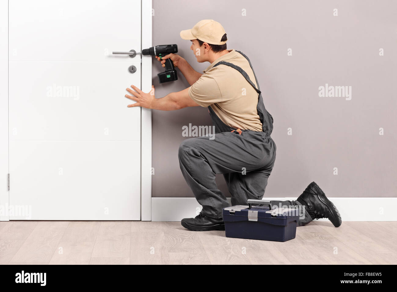 Young male locksmith installing a lock on a new white door with a hand drill - Stock Image