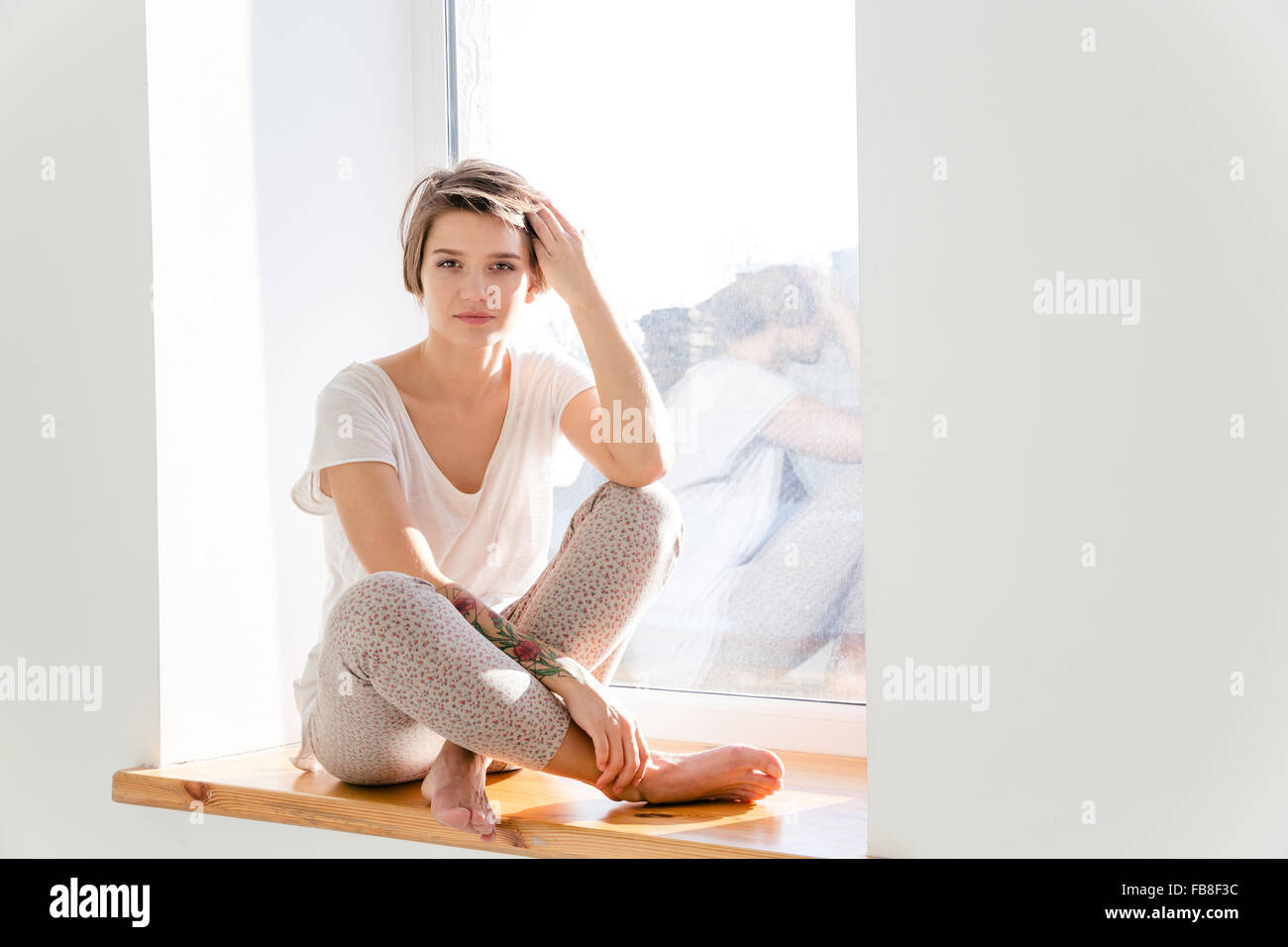 Cute Lovely Young Woman With Short Haircut In Pajamas Sitting On