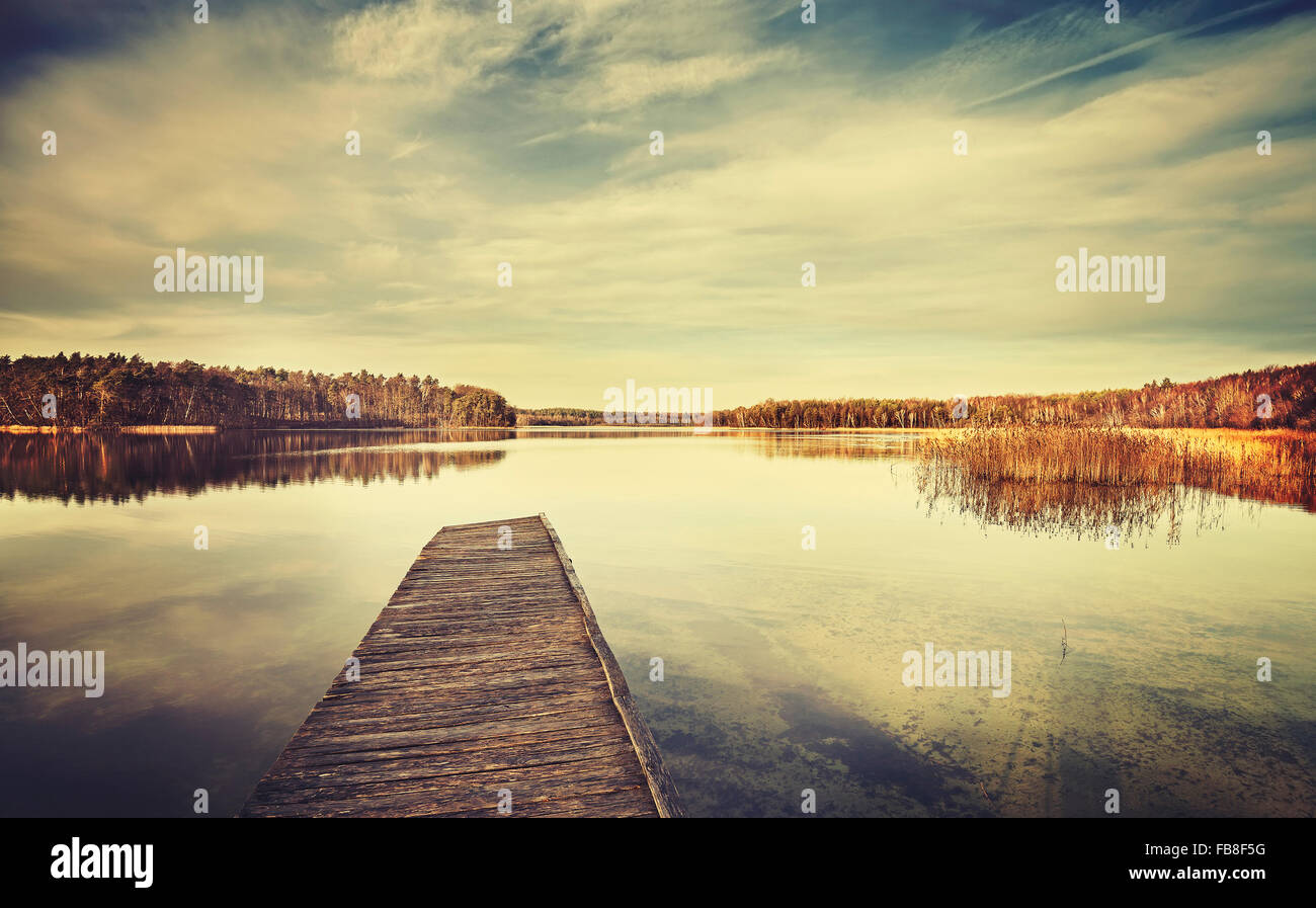 Vintage stylized picture of a lake and wooden pier. - Stock Image