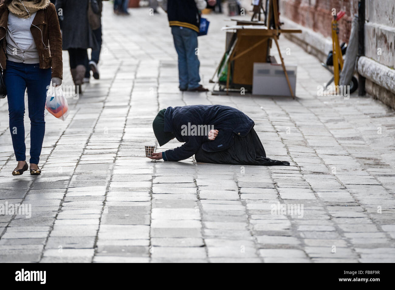 A woman covered in black on her knees with head bowed down waiting for charity. Venice, Italy. - Stock Image