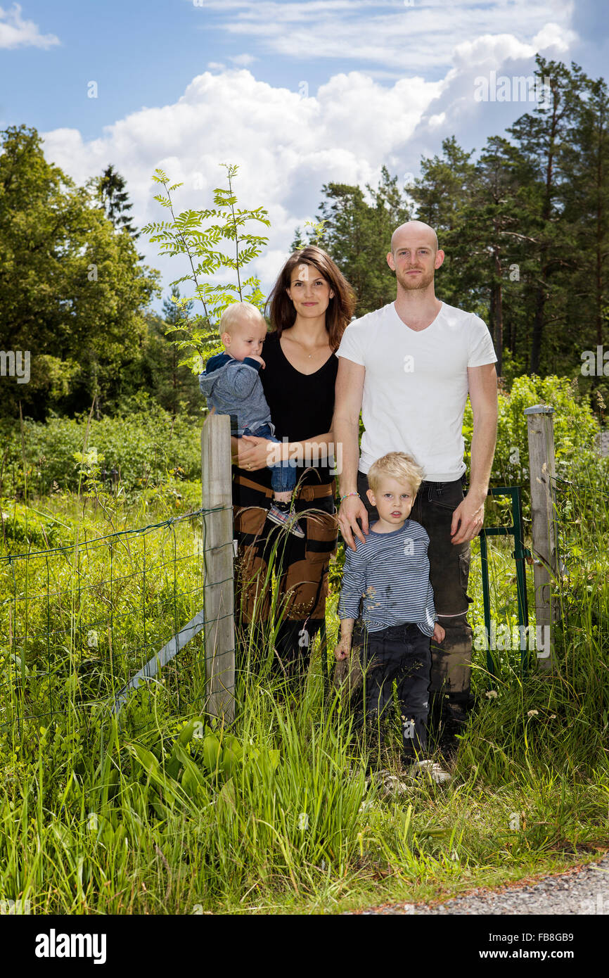 Sweden, Stockholm, Uppland, Nacka, Family with two children (18-23 months, 4-5) standing among lush foliage - Stock Image