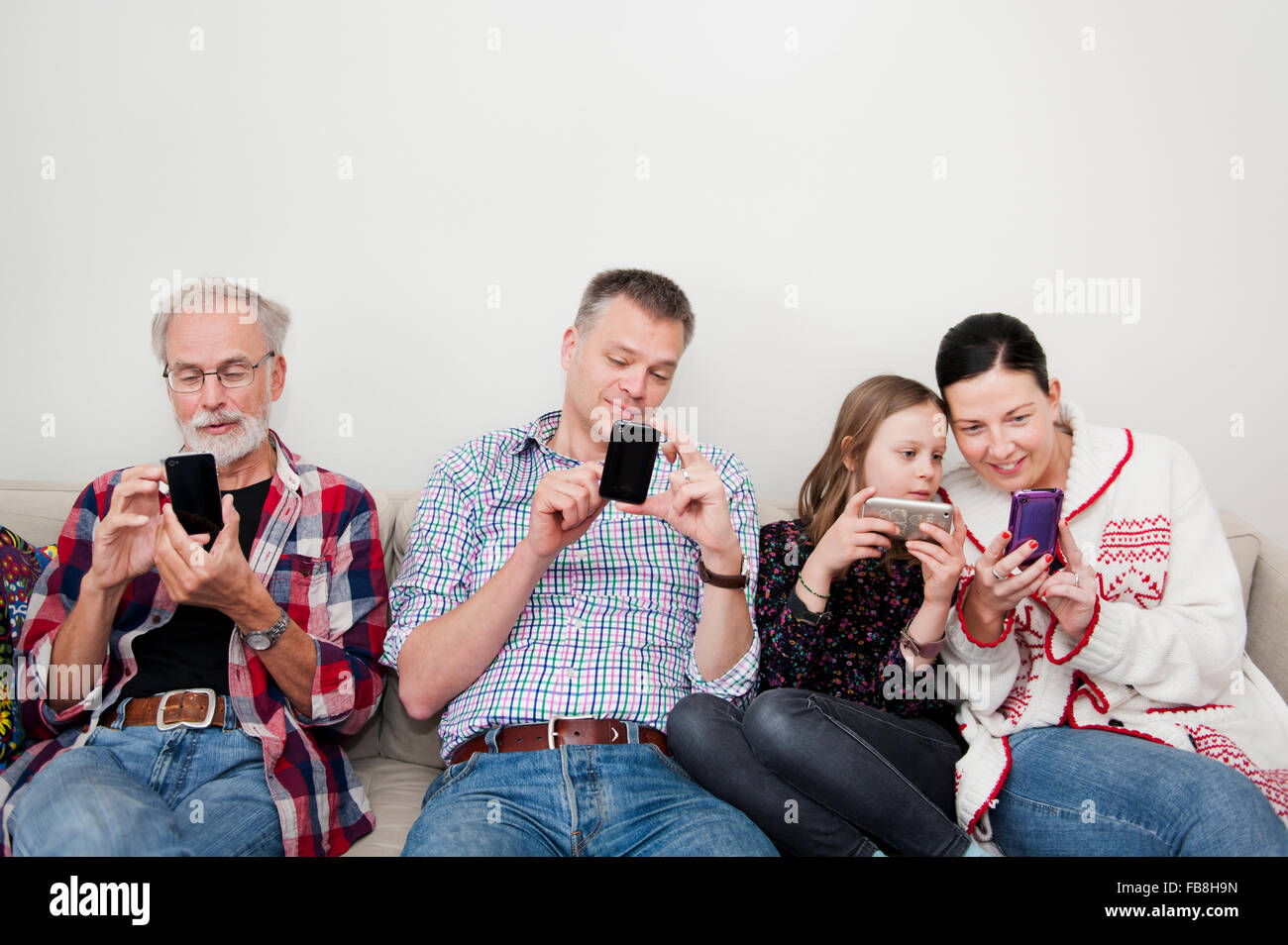 Girl (8-9) texting with family on sofa - Stock Image