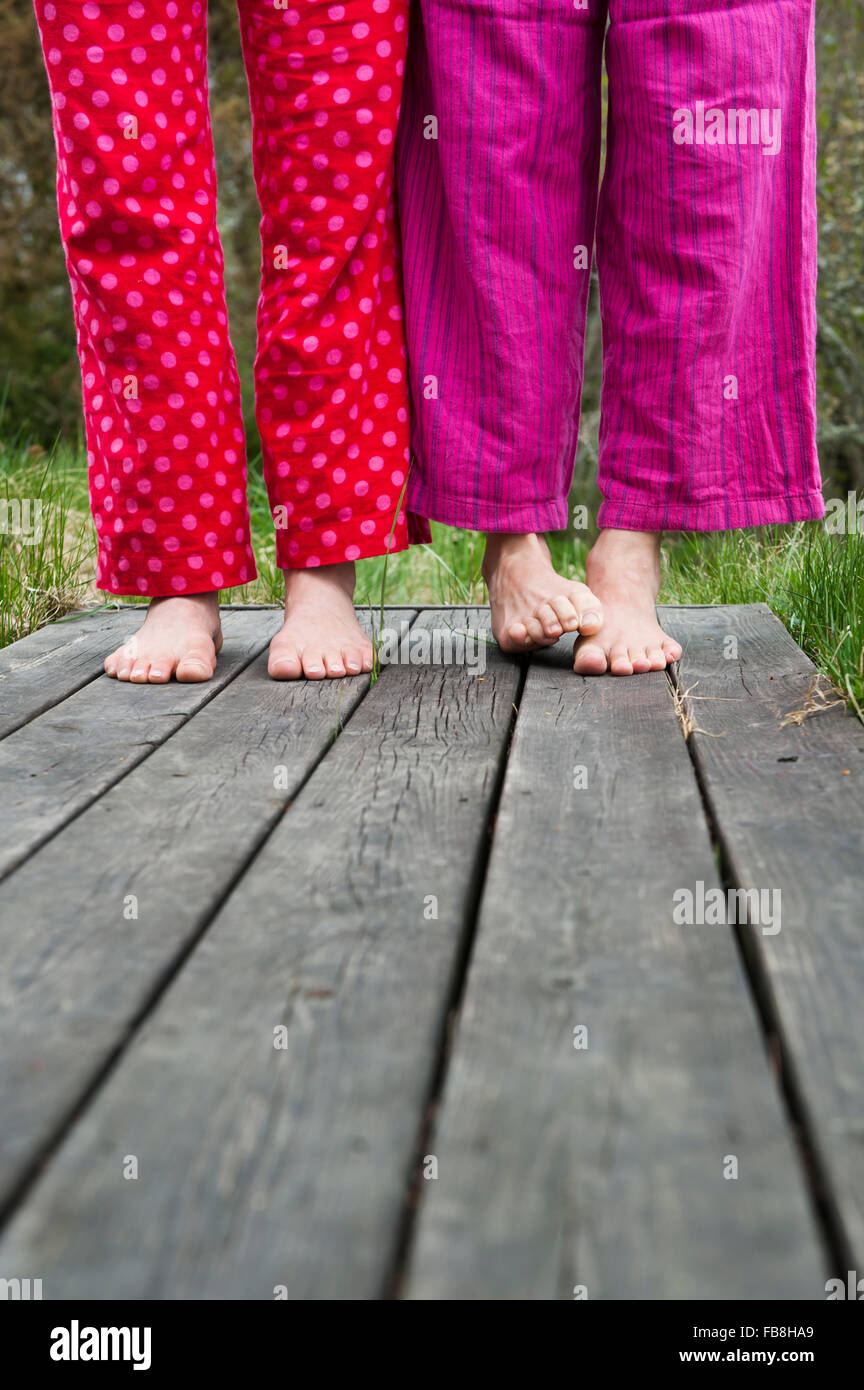 Sweden, Ostergotland, Vikbolandet, Low-section of couple in pajamas - Stock Image