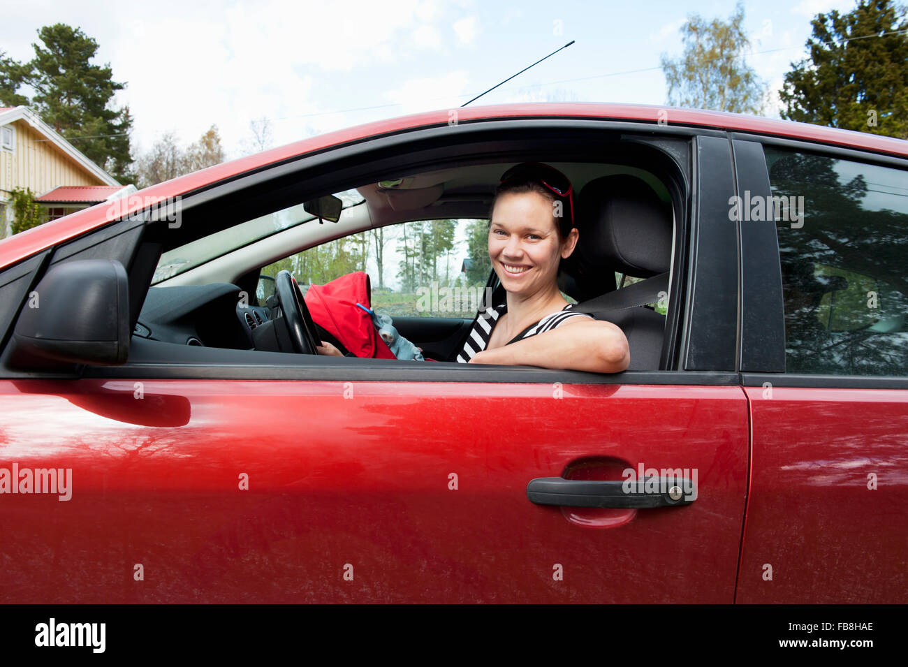 Sweden, Ostergotland, Vikbolandet, Woman going on road trip with her baby girl (6-11 months) - Stock Image