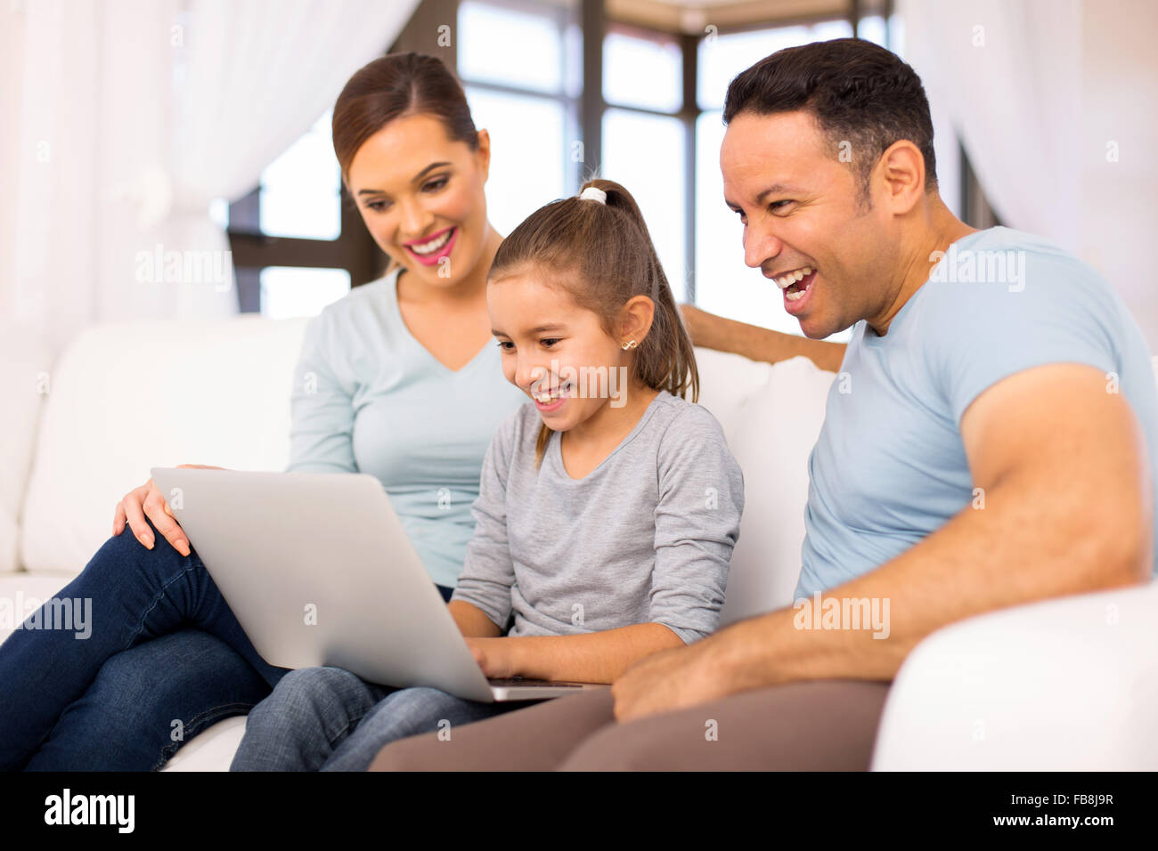 modern family using laptop computer at home - Stock Image