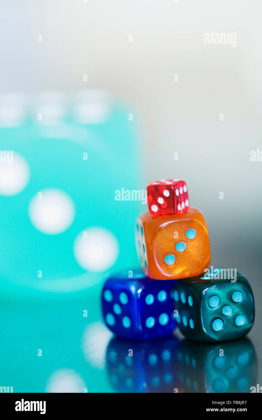 Multi colored dice on table - Stock Image