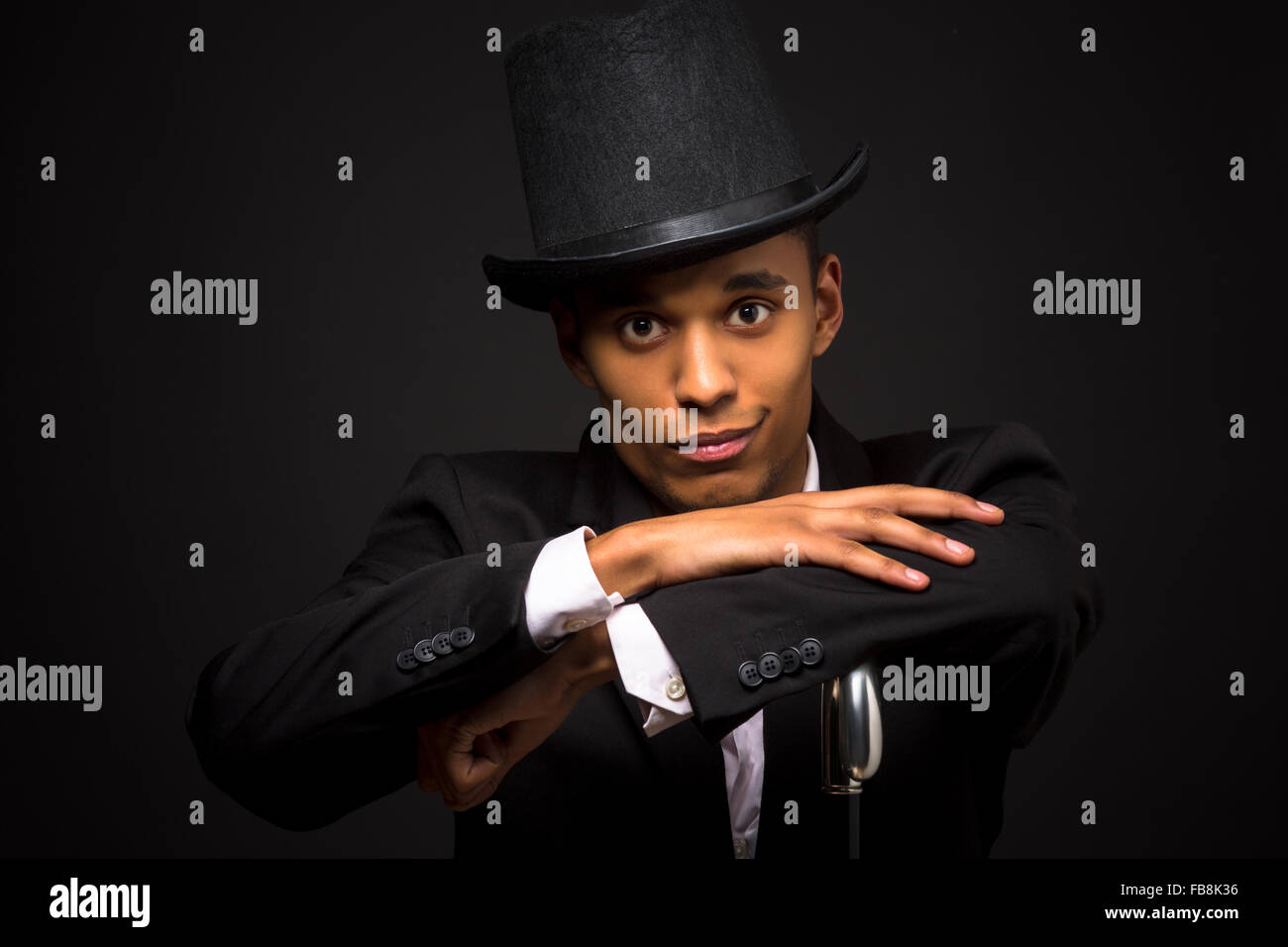 Handsome man in top hat posing with cane Stock Photo