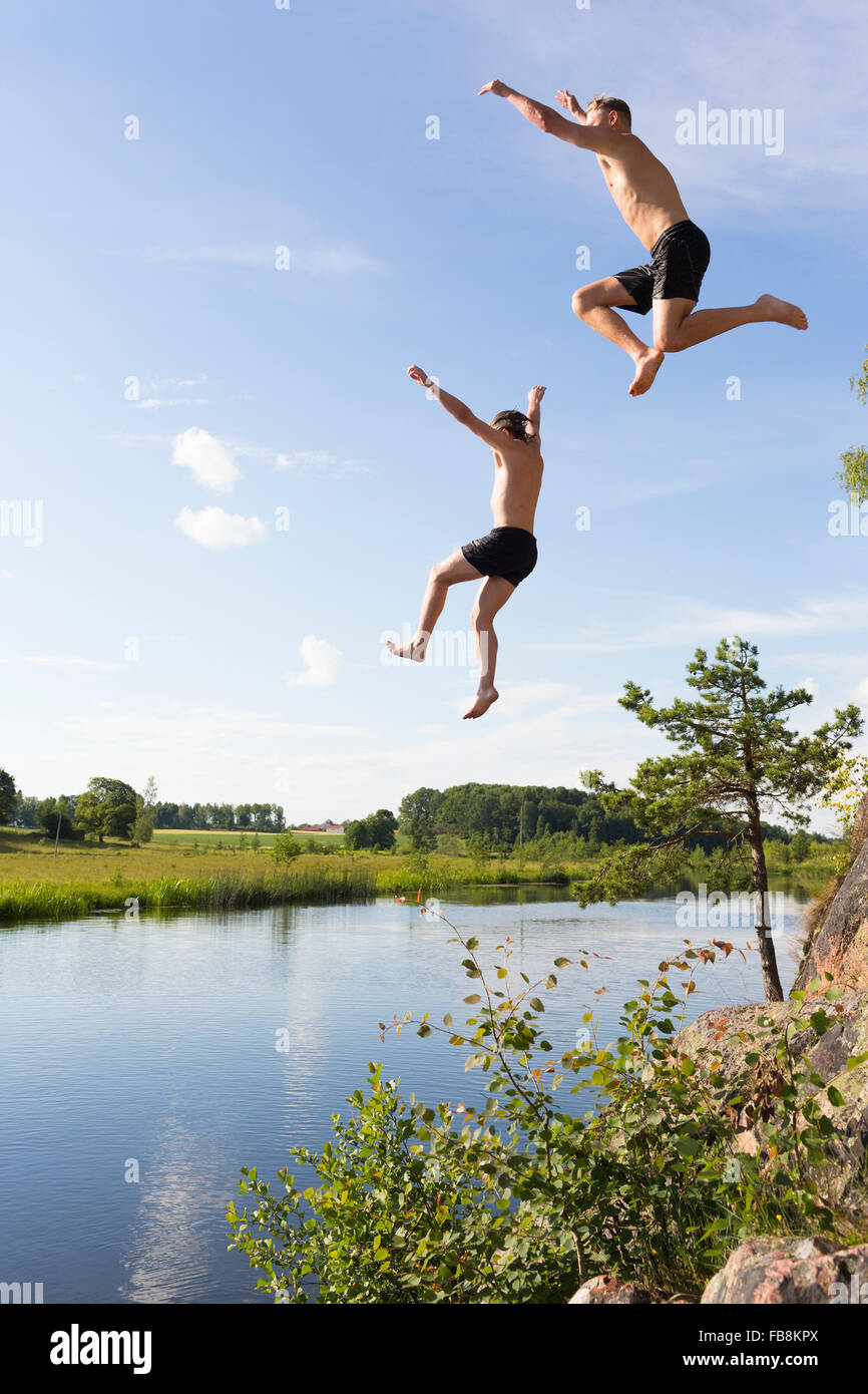 Sweden, Ostergotland, Mjolby, Young man and teenage boy (16-17) jumping into Svartan River - Stock Image