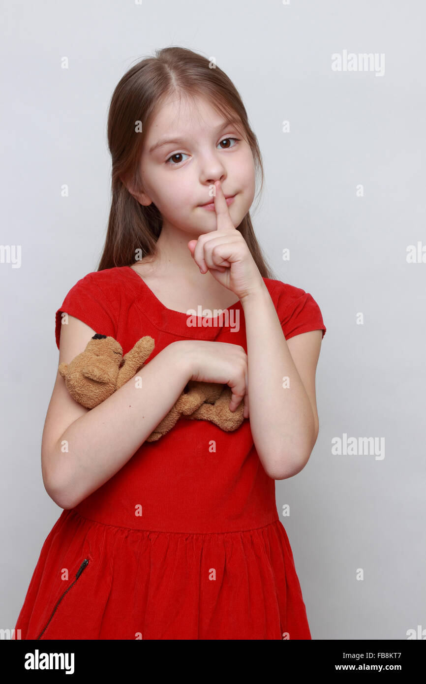 22b426c77cb54 Beautiful little girl in red fashion dress holding lovely toy teddy bear