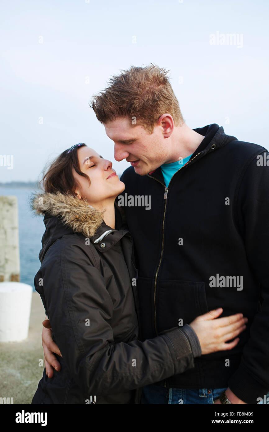 Sweden, Skane, Arild, Young couple embracing - Stock Image