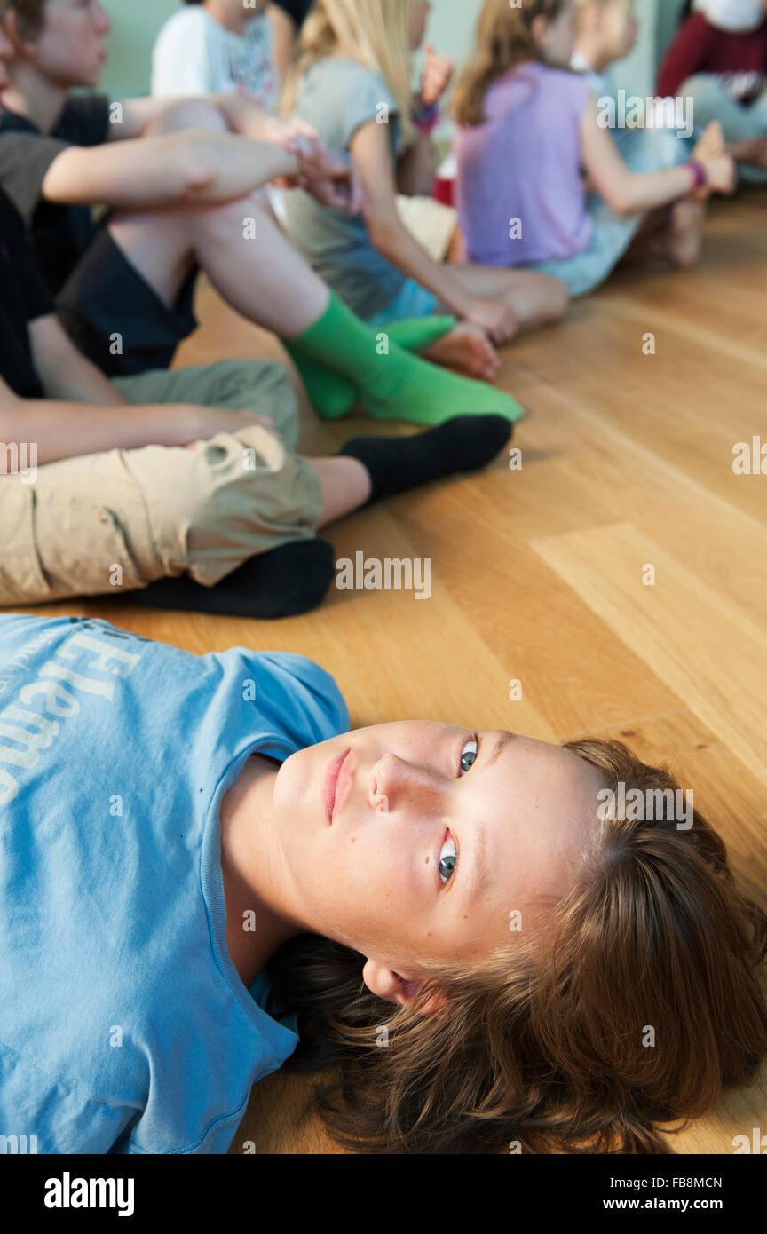 Sweden, Boy (12-13) lying on hardwood floor - Stock Image